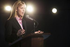 Businesswoman Giving Speech At Podium In Auditorium